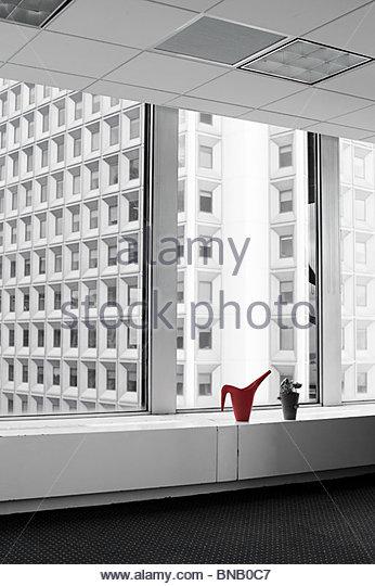 Gießkanne und Pflanze auf Büro-Fensterbank Stockbild