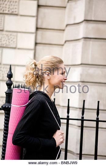 Ein Mitte Erwachsene Frau, die eine Yoga-Matte, Wandern Stockbild