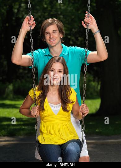 Junge glückliche Paar in ihren frühen dreißiger Jahren, die Spaß auf einer Schaukel am Kinderspielplatz Stockbild