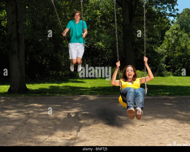 Junges Paar in den Dreißigern, die Spaß auf einer Schaukel am Kinderspielplatz Stockbild
