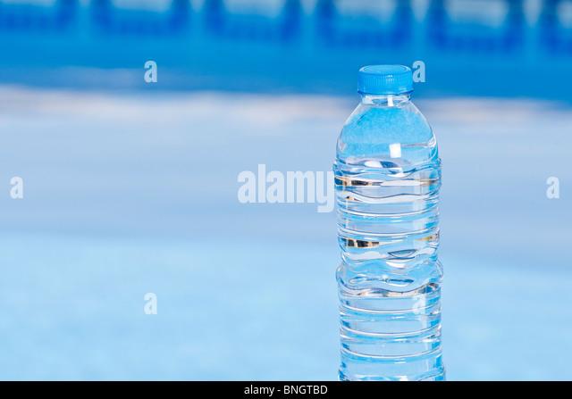 Schuss eine Flaschenwasser neben dem Pool Stockbild