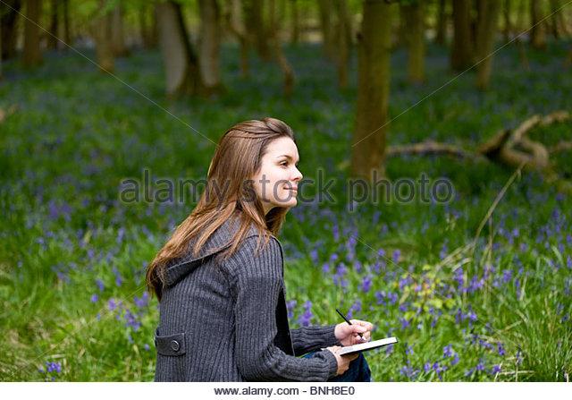 Eine junge Frau sitzt, hält eine Skizze/notebook Stockbild