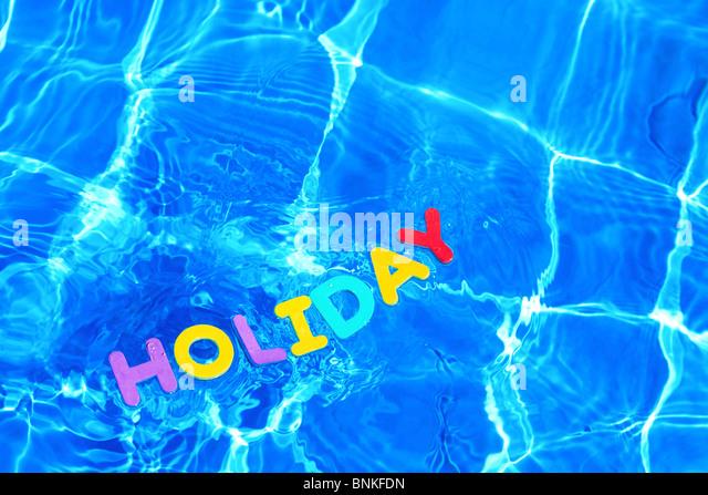 Das Wort Urlaub gemacht aus Schaum schwimmt auf der Wasseroberfläche eines Schwimmbades Stockbild