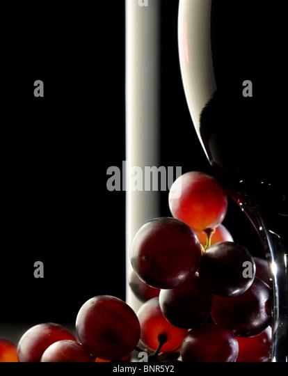Nahaufnahme von roten Trauben und einem Glas / Flasche Rotwein Stockbild
