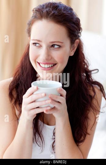 Schöne Frau trinkt eine Tasse Kaffee im Bett Stockbild