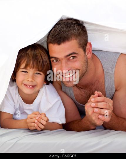 Vater und Sohn gemeinsam unter der Bettwäsche Stockbild
