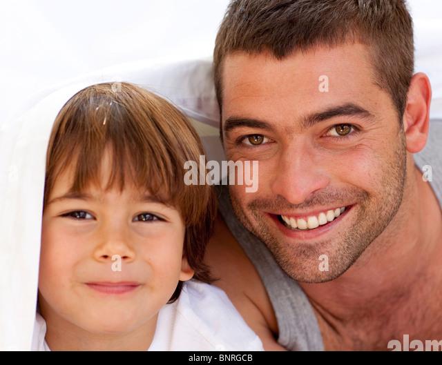 Porträt von Vater und Sohn unter der Bettwäsche Stockbild