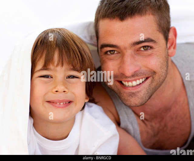 Vater und Sohn spielen unter der Bettwäsche Stockbild