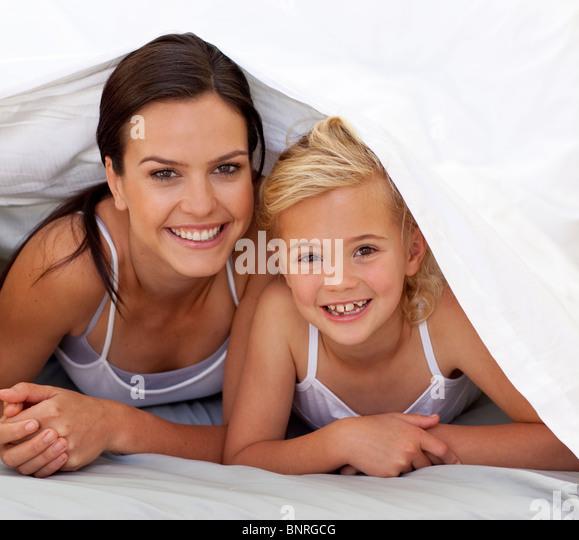 Mutter und Tochter unter die Bettwäsche Stockbild