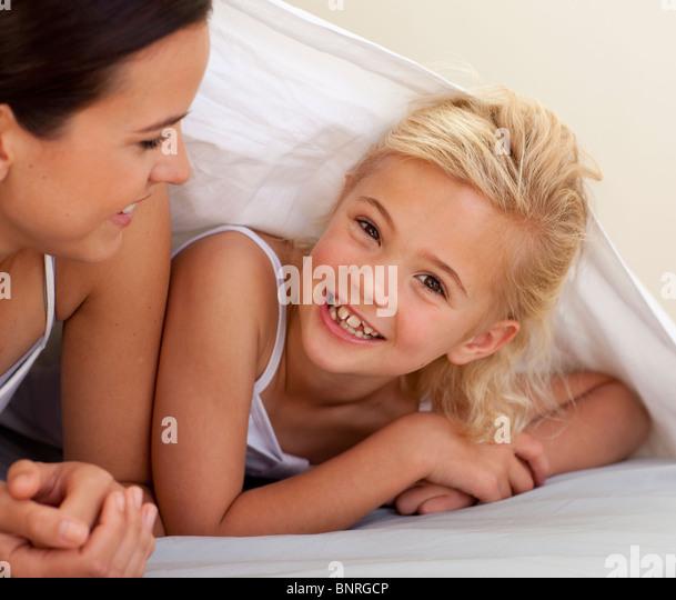 Mutter und Tochter spielen unter der Bettwäsche Stockbild