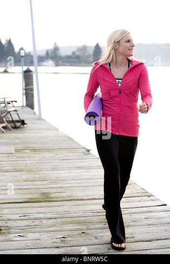 Eine junge Frau zu Fuß auf einem Dock über Lake Washington und tragen eine gerollte Yoga-Matte. Stockbild