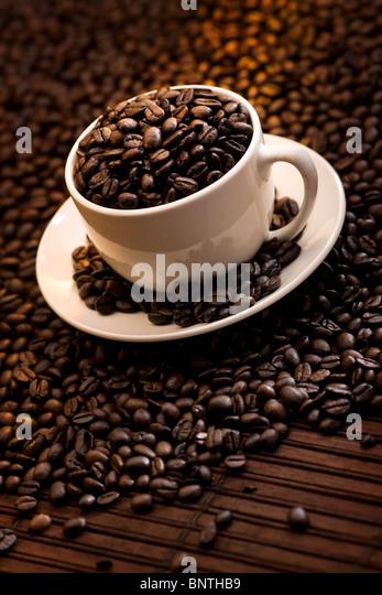 Tasse mit köstlichen gerösteten Kaffeebohnen gefüllt Stockbild