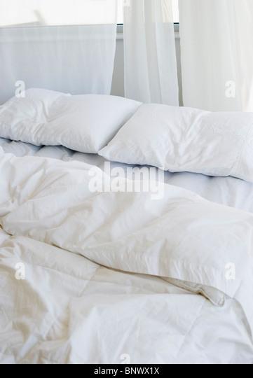 Bett mit weißer Bettwäsche Stockbild