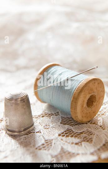 Vintage-Baumwolle Reel mit Nadel und Silber Fingerhut auf weißer Spitze Stockbild