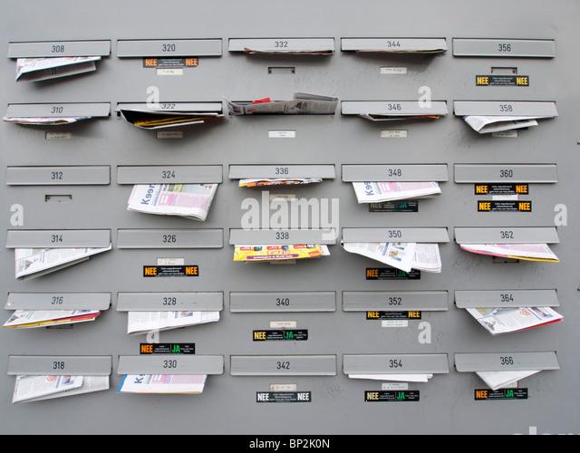 Mehrfamilienhaus Briefkästen voll von Junk-e-Mail in Amsterdam Niederlande Stockbild