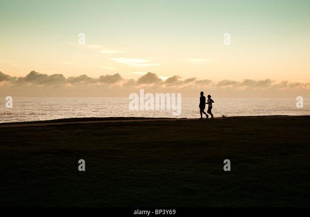 Zwei Jogger Silhouette direkt am Meer mit Sonne hinter Wolken am Horizont Stockbild