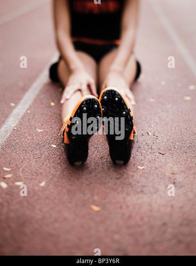 US-amerikanischer Sprinter Mädchen dehnen Beine auf der Spur Stockbild