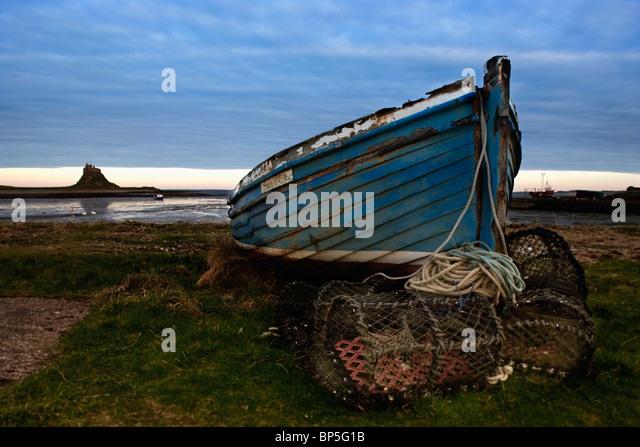 Northumberland, England; Eine verlassene Boot und fallen am Ufer mit Blick auf Lindisfarne (Holy Island) Stockbild