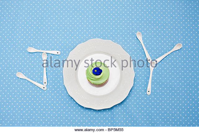 """Teelöffel und Platte mit Cupcake Schreibweise """"Freude"""" auf Tischdecke Stockbild"""