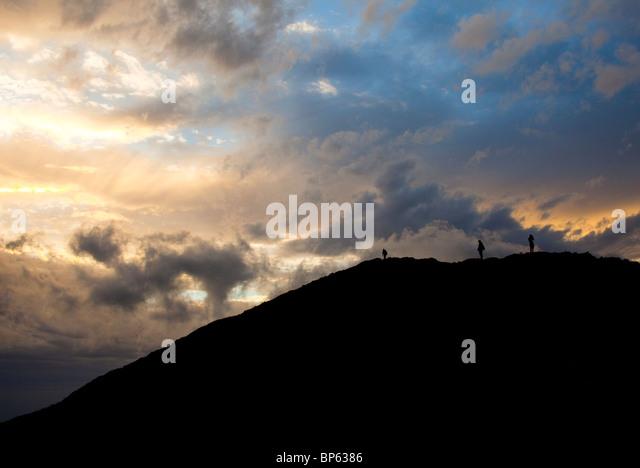 Silhouette der Wanderer auf einem Berg in einem bewölkten Sonnenuntergang Stockbild