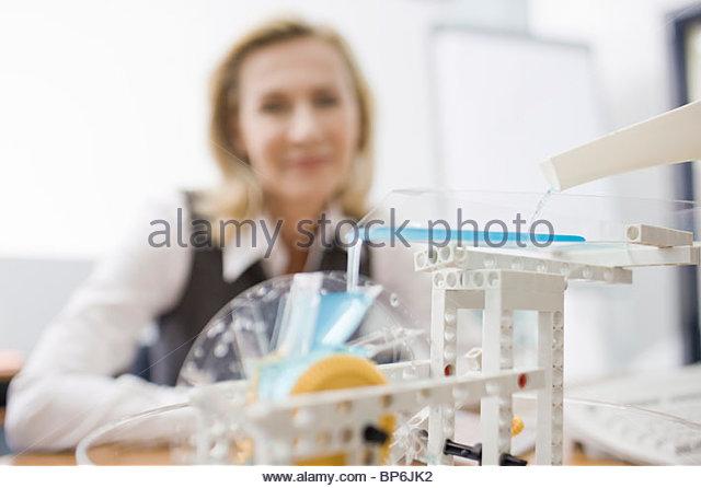 Eine Geschäftsfrau auf der Suche auf ein Modell von einem Wasserrad Stockbild