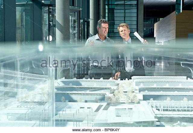 Zwei Geschäftsleute diskutieren ein architektonisches Modell Stockbild