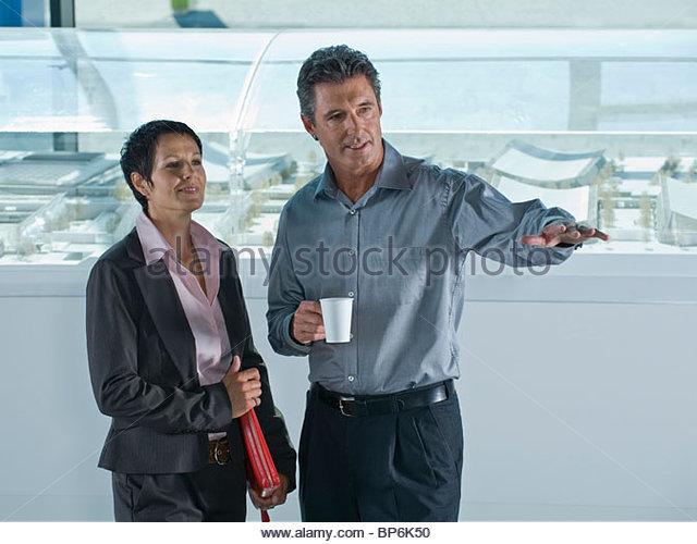 Ein Geschäftsmann und Geschäftsfrau diskutieren Architekturmodelle Stockbild