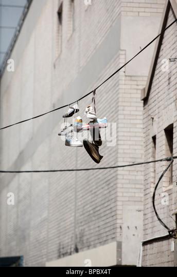 Schuhe hängen von ihrer Schnürsenkel auf einem Draht in der Stadt Stockbild