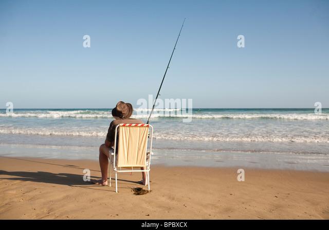 Fischer sitzen an einem Strand Stuhl Surf Casting im Ozean Stockbild