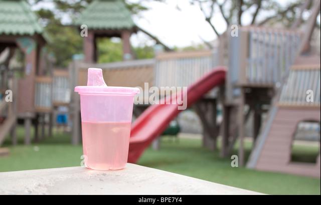 Rosa sippy Tasse mit Spielplatz im Hintergrund Stockbild