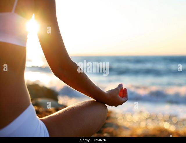 Körper eines schönen Mädchens in einer Meditation am Strand Stockbild