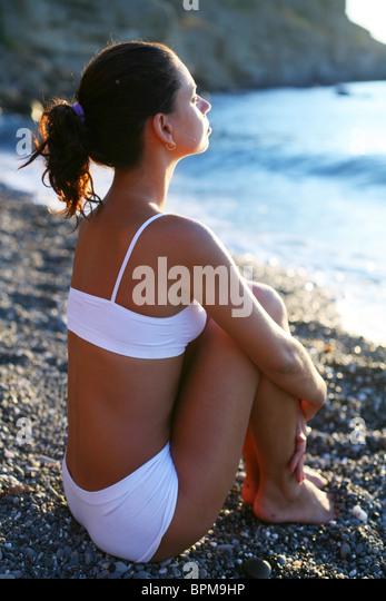 Frau am Strand bei Sonnenuntergang zu meditieren. Stockbild