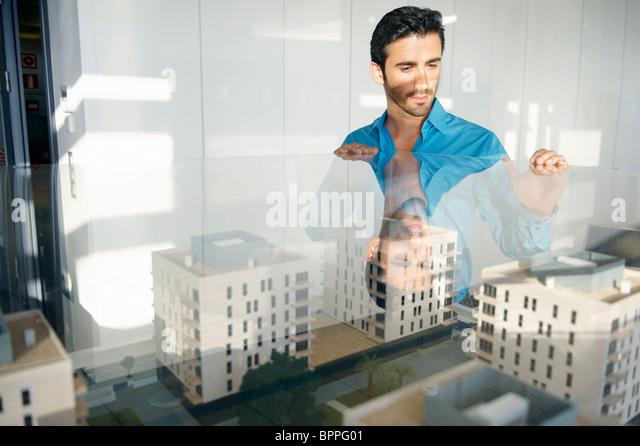 Mann sucht am Architekturmodell Stockbild