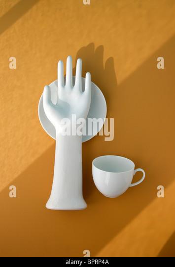 Weißes Porzellan Hand mit Tasse und Untertasse auf gelb mit Schatten Stockbild