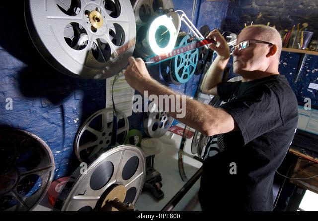 Ein Filmvorführer in einem Kino richtet ein 35mm-Film. Stockbild