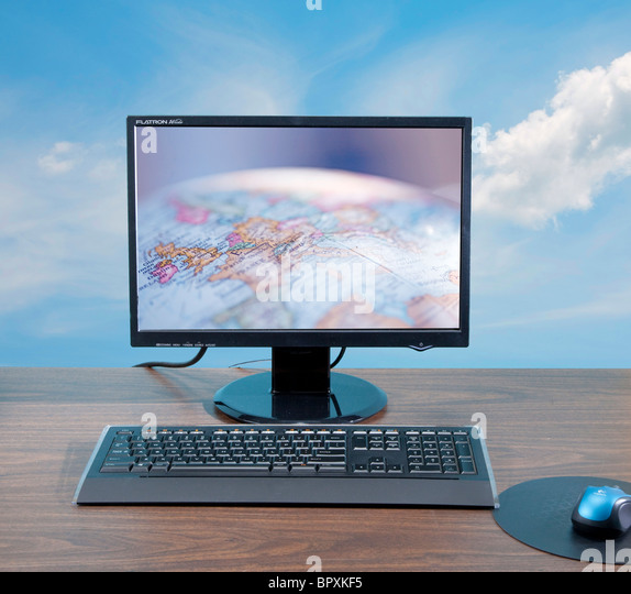 Globus am Computer-Bildschirm am Schreibtisch Stockbild