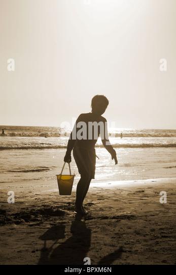 Sepia Bild des jungen laufen am Strand mit Eimer in der Nähe des Ozeans Stockbild