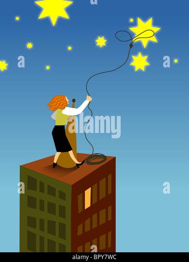 Eine Geschäftsfrau mit dem Lasso eines Stern vom Himmel Stockbild