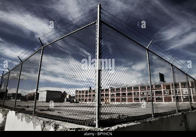 Ein Zaun vor einem Fabrikgebäude mit einem dramatischen Himmel. Stockbild