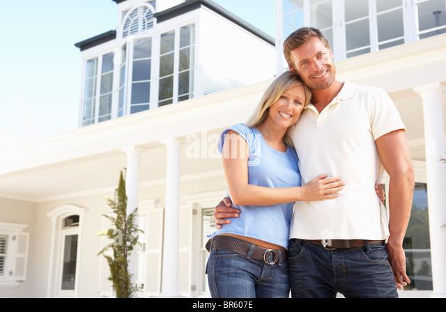 Junge Paar stehen außen Traumhaus Stockbild