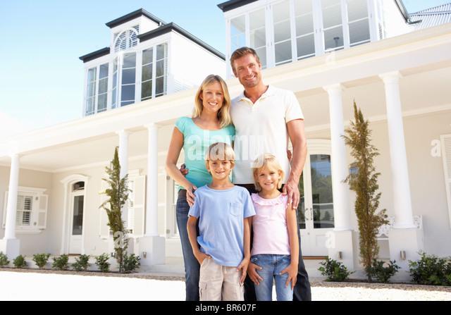 Junge Familie stehen außen Traumhaus Stockbild