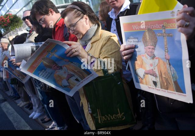 Katholiken lesen Gratiszeitungen Massen außerhalb Westminster Cathedral, bevor Papst Benedict XVI ankommt. Stockbild