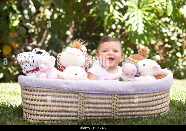 Glückliches Baby in Korb voller Plüschtiere Stockbild