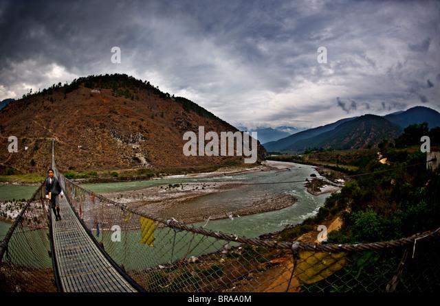 Ein Student überquert Bhutans längste Hängebrücke, Panakha, Bhutan, Himalaya, Asien Stockbild