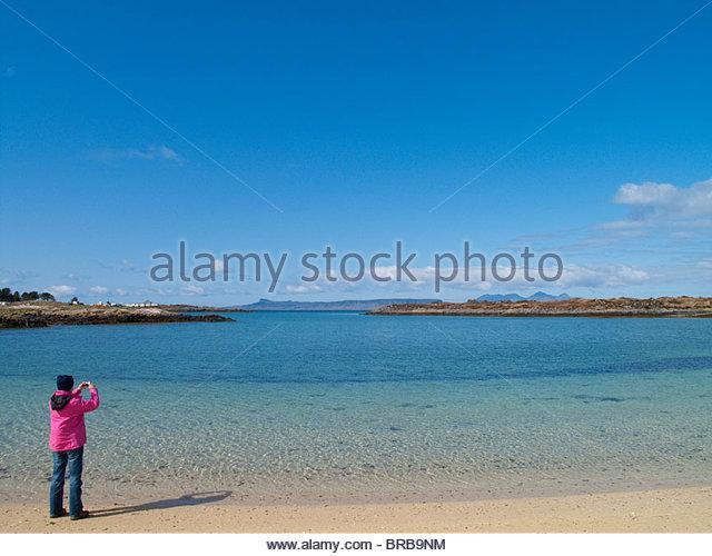 Frau nehmen Foto von ruhigen Ozean unter blauem Himmel Stockbild