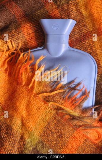 Eine blaue heiße Flasche Wasser teilweise von einem rot karierten Wolldecke mit Fransen bedeckt. Stockbild