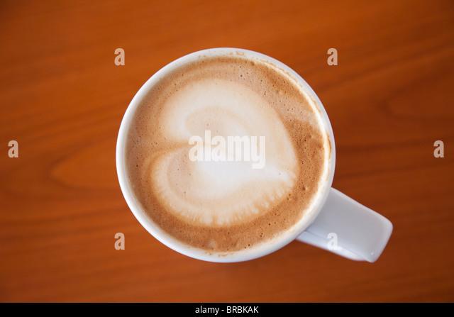 Tasse Cafe Latte Kaffee mit einer Herzform in den Schaum auf einem Holztisch von oben Stockbild