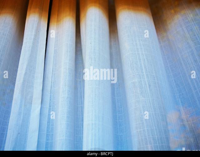 weiße und braune Vorhänge hängen im Schaufenster Stockbild