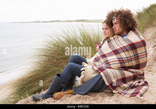 Teenager-paar sitzen In Sanddünen In Decke gehüllt Stockbild