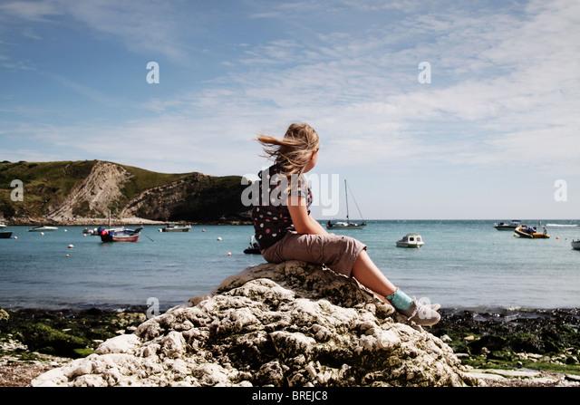 Mädchen sitzen auf einem Felsen bei Lulworth Cove, UK Stockbild